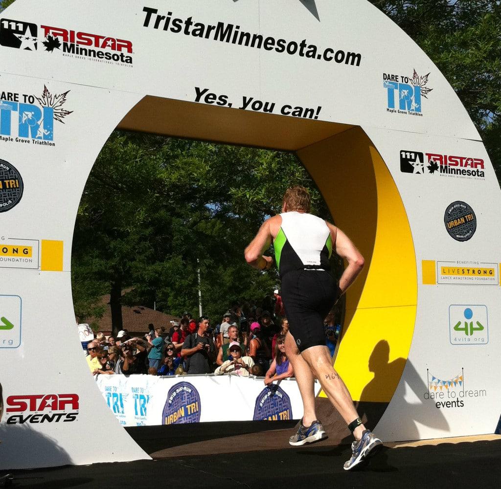 A senior triathlete running across the finish line of the Maple Grove Minnesota triathlon