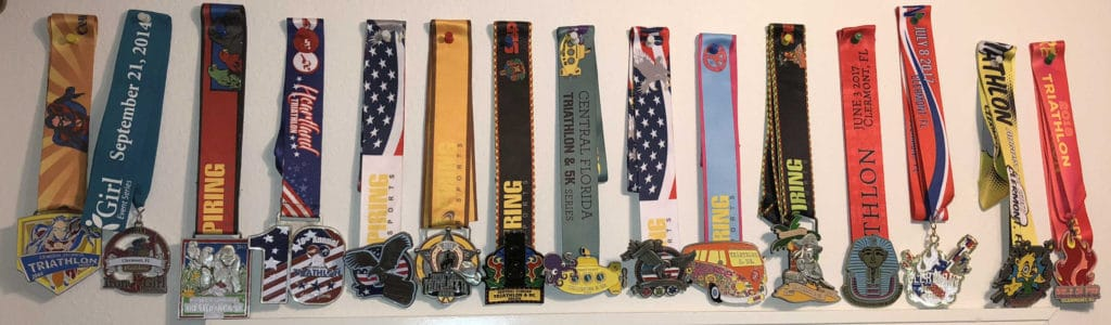 Pat Johnson prepared for her first sprint triathlon at age 70 in less than 30 days. Since then, she has created a collection of finisher medals.  Included is one from Pat's first sprint triathlon.
