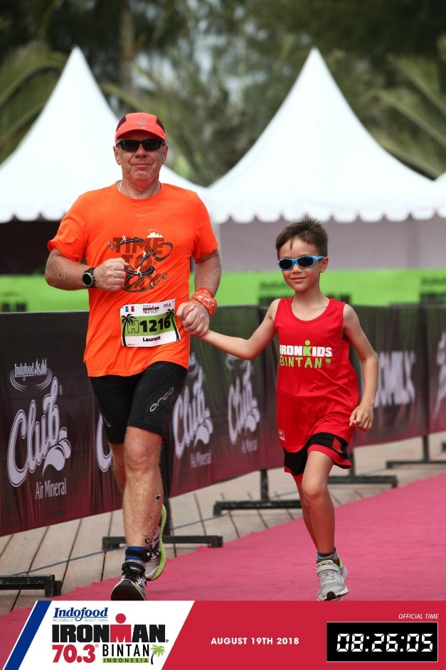 Laurent Labbe and son on the final dash to the finish line at Ironman 70.3 Bintan, Indonesia