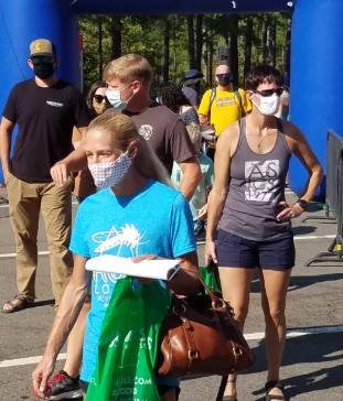 masked triathletes waiting for packet pickup during the COVID-19 pandemic